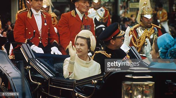 Queen Elizabeth II of England and Prince Philip wave to crowds as they ride in open carriage to investiture of son Prince Charles as Prince of Wales...