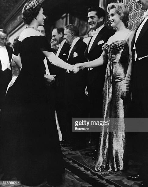 Queen Elizabeth II of England offers a gloved hand to Hollywood glamour girl Marilyn Monroe Miller during the Queen's visit with celebrities at the...