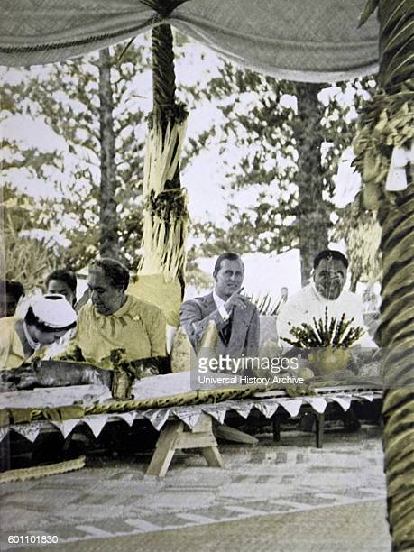 Queen Elizabeth II of England visits Queen Salote of Tongo during a royal tour of 1953 She is seated at a banquet with the Queen of Tonga and the...
