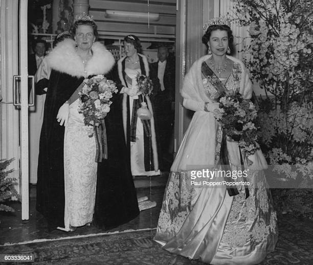 Queen Elizabeth II of Great Britain and Queen Juliana of the Netherlands both wearing evening gowns and tiaras, carry bouquets as they leave the...