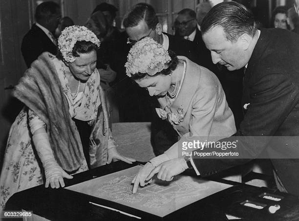 Queen Elizabeth II of Great Britain and Queen Juliana of the Netherlands view a large reproduction of the Royal Cypher set in diamonds, with director...
