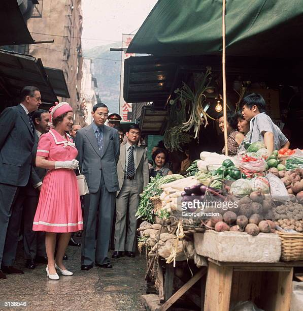 Queen Elizabeth II of Great Britain at a market stall during a royal tour of Hong Kong