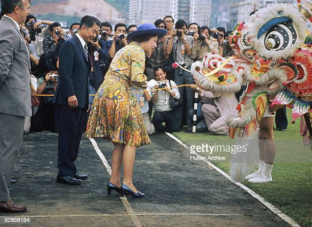 Queen Elizabeth II of Great Britain meets a Chinese dragon in Hong Kong during the Royal Tour of 1975.