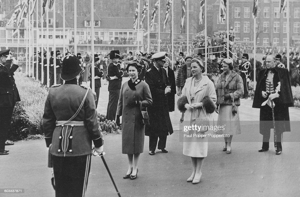 Queen Elizabeth II of Great Britain (front, left) stands with Queen Juliana of the Netherlands, with Prince Philip (centre, wearing a hat) and Princess Irene (second left) in the background as they greet the Regimental Color of the Prins Hendrikkade in Amsterdam, Netherlands on March 26th 1958.