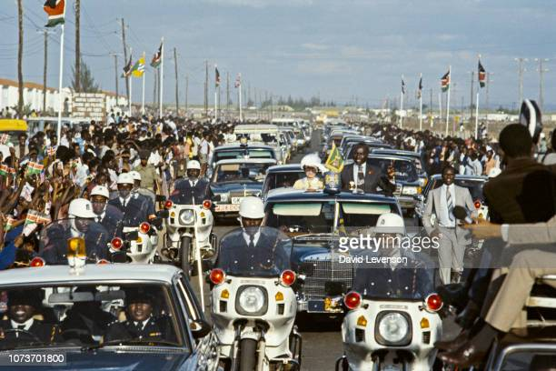 Queen Elizabeth II on a car escorted by Kenyan police with with President Daniel Arap Moi as she visits Nairobi Kenya 10th November 1983