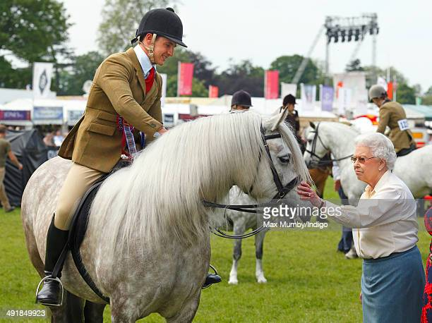 Queen Elizabeth II pats her horse 'Balmoral Erica' after it came second in the Ridden Mountain and Moorland Class on day 4 of the Royal Windsor Horse...