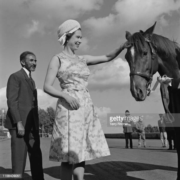 Queen Elizabeth II patting on the forehead of a horse while Ethiopian emperor Haile Selassie is standing next to her during her visit to Ethiopia,...