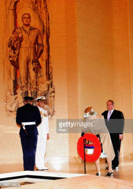 Queen Elizabeth II pays her respect and lays a wreath at the Tomb of the Unknown soldier during a visit to the Australian War Memorial on October 25...