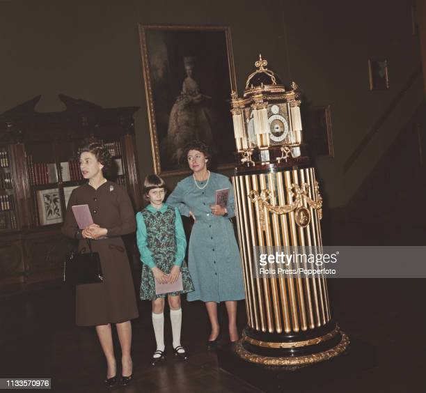 Queen Elizabeth II pictured on left with Princess Margaret Countess of Snowdon and her daughter Sarah ArmstrongJones as they stand beside an ornate...