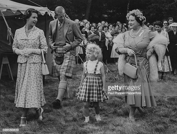 Queen Elizabeth II pictured together with Prince Philip Duke of Edinburgh Queen Elizabeth the Queen Mother and little Princess Anne as they attend a...