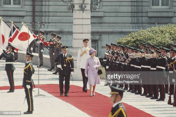 Queen Elizabeth II pictured walking along a red carpet outside the Akasaka Palace in Tokyo as a military band plays during a State visit to Japan in...