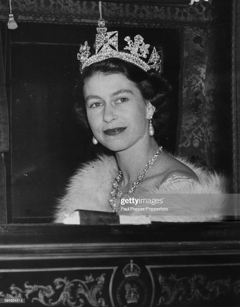 Queen Elizabeth II pictured wearing a crown, necklace and pearl earrings as she sits in the Irish State Coach, on her return to Buckingham Palace following the state opening of Parliament in London, November 4th 1952.