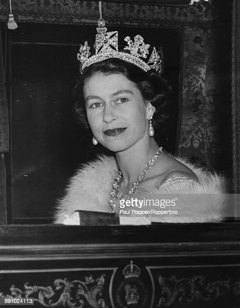 Queen Elizabeth II pictured wearing a crown necklace and pearl earrings as she sits in the Irish State Coach on her return to Buckingham Palace...