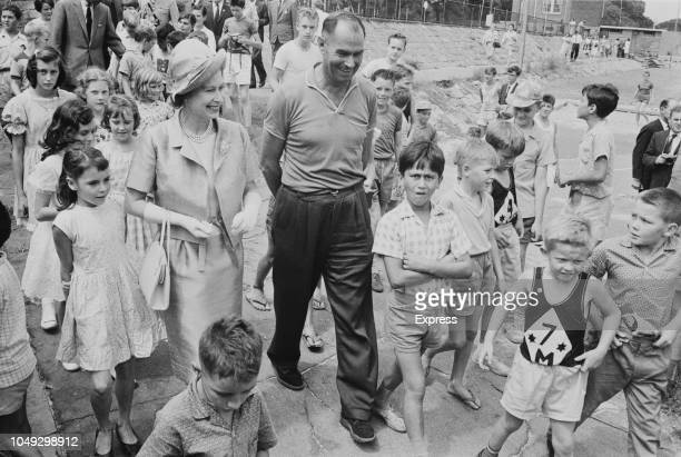 Queen Elizabeth II pictured with a guide surrounded by school children at a children's playground in Sydney during a Commonwealth visit to Australia...
