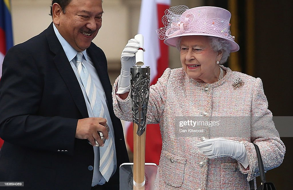 Queen Elizabeth II places a message for the host city in the Queen's Baton with HRH Prince Imran, President of the Commonwealth Games Federation on October 9, 2013 in London, England. After presenting the baton to Queen Elizabeth II, the relay will continue it's journey visiting all 70 competing nations and territories ahead of the Commonwealth Games in Glasgow in 2014.