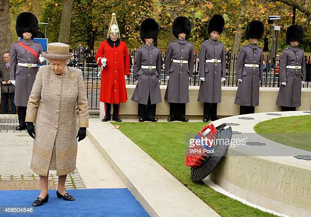 Queen Elizabeth II places a wreath of poppies at the new Flanders Field Memorial outside the Guards Chapel on November 6 2014 in London England