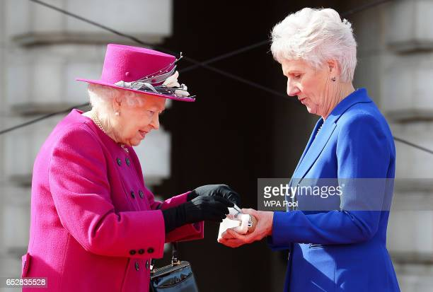 Queen Elizabeth II places her message into the relay baton which is held by Louise Martin the President of the Commonwealth Games Federation during...