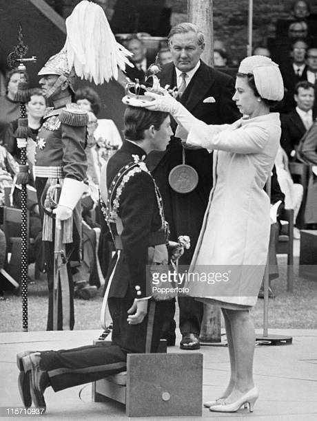 Queen Elizabeth II places the coronet on the head of her son Prince Charles during his investiture as Prince of Wales at Caernarvon Castle on 1st...