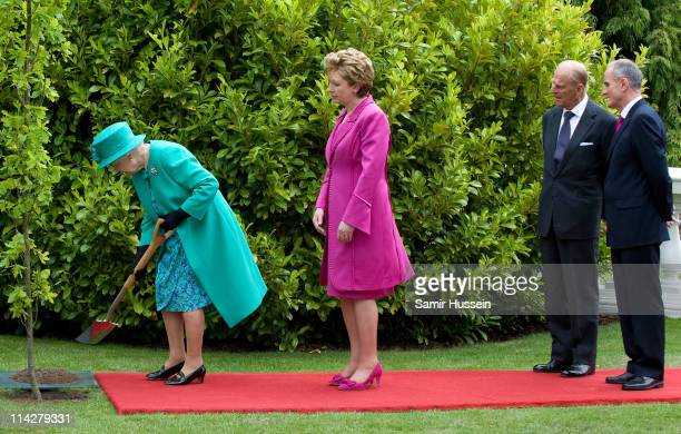 Queen Elizabeth II plants a tree as Irish President Mary McAleese, Prince Philip, Duke of Edinburgh and Martin McAleese look on at Aras an Uachtarain...