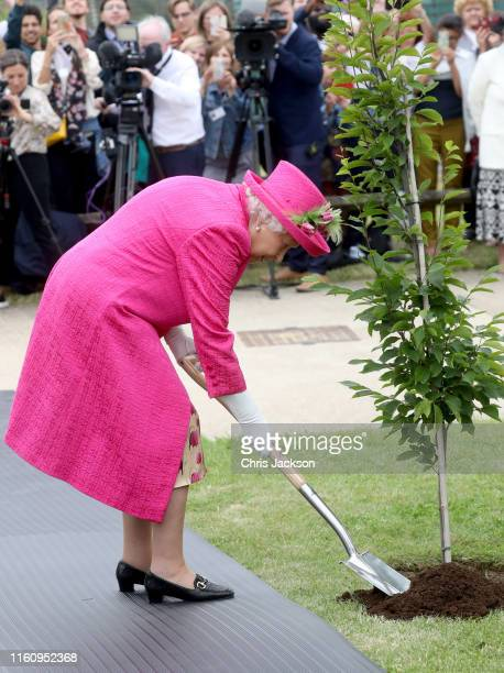Queen Elizabeth II plants a tree during a visit to the NIAB on July 09 2019 in Cambridge England