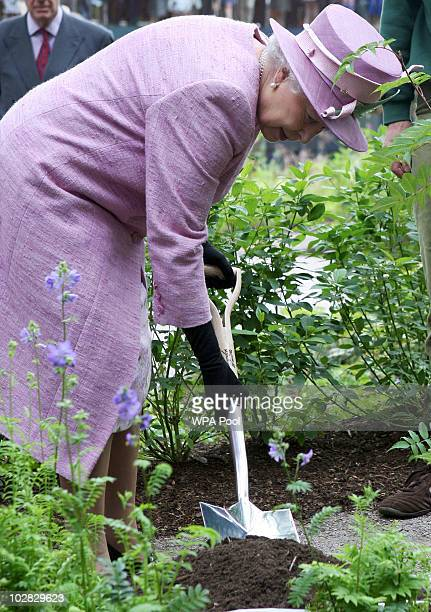 Queen Elizabeth II plants a tree during her visit to officially open a Visitor Centre at the Royal Botanic Garden Edinburgh on July 12 2010 in...