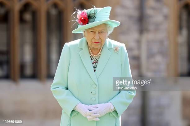 Queen Elizabeth II poses after awarding Captain Sir Thomas Moore with the insignia of Knight Bachelor at Windsor Castle on July 17, 2020 in Windsor,...