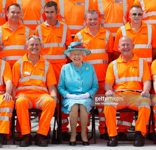 Queen Elizabeth II poses for a group photograph with Network Rail construction workers after opening the newly redeveloped Reading Railway Station on...