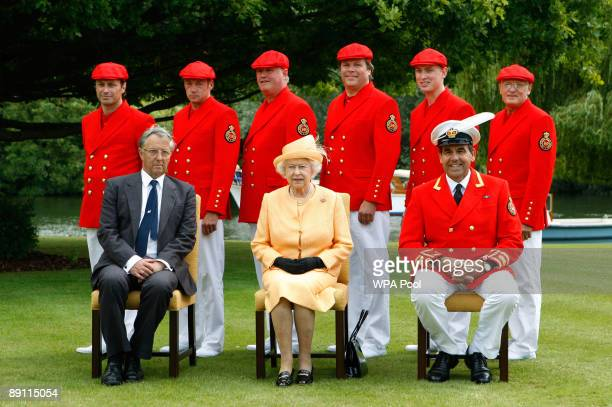 Queen Elizabeth II poses for a photograph with Swan Warden Professor Christopher Perrins and Swan Marker David Barker at Oakley Court on the banks of...