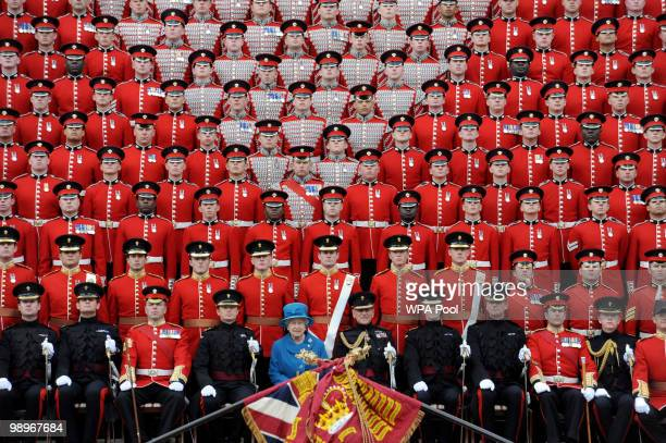 Queen Elizabeth II poses for an official photograph with the Grenadier Guards in Wellington Barracks after presenting the regiment with their new...