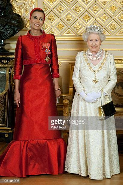 Queen Elizabeth II poses with Sheikha Mozah bint Nasser Al Missned the wife of Qatar's Emir Sheikh Hamad bin Khalifa al Thani before a banquet held...