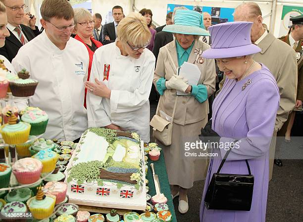 Queen Elizabeth II prepares to cut a special Jubilee cake designed by students at Yeovil College as she visits Nine Springs Park on May 2 2012 in...