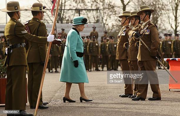 Queen Elizabeth II prepares to resheath a Gurkha soldier's sword as part of his commissioning ceremony to become a Late Entry Officer on her visit to...
