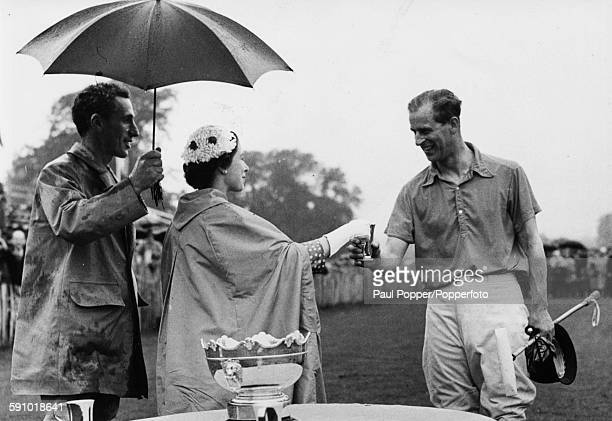 Queen Elizabeth II presents a cup to her husband Prince Philip Duke of Edinburgh as captain of the winning team after the novice polo final match at...