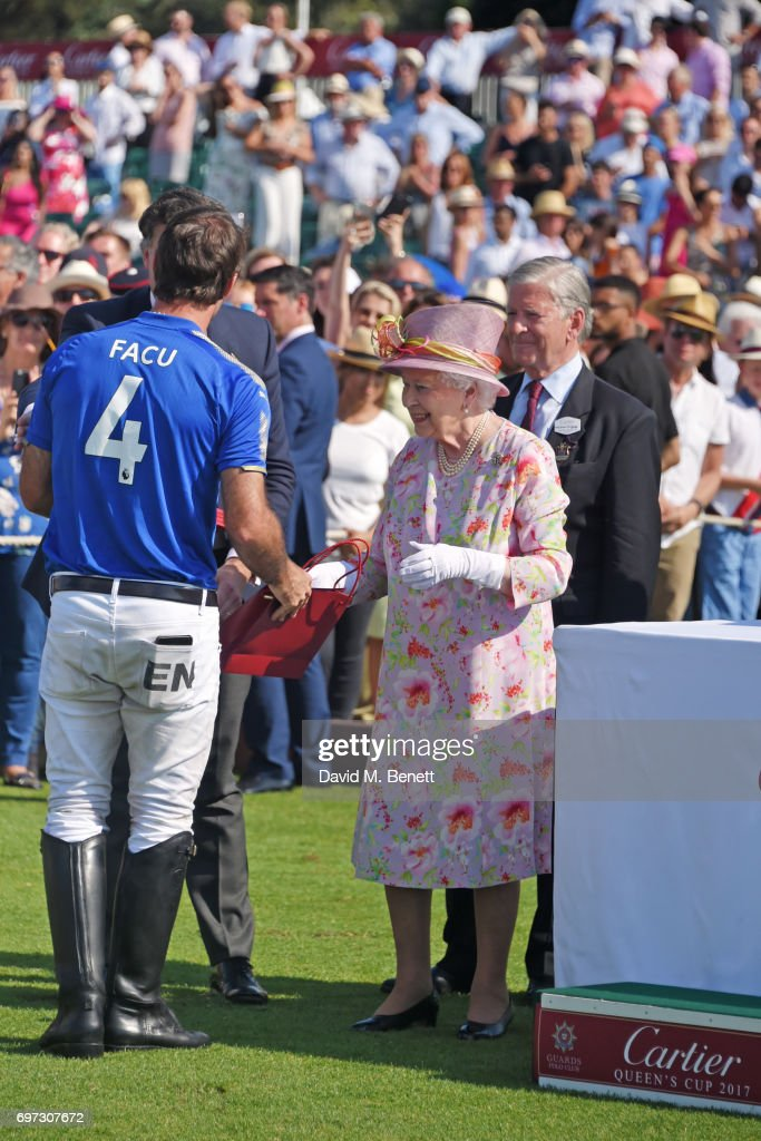 Queen Elizabeth II (C) presents a prize at the Cartier Queen's Cup Polo final at Guards Polo Club on June 18, 2017 in Egham, England.