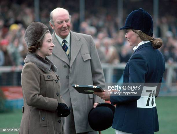 Queen Elizabeth II presents Clarissa Strachan of Great Britain with the trophy for winning the under25 award during the Badminton Horse Trials in...