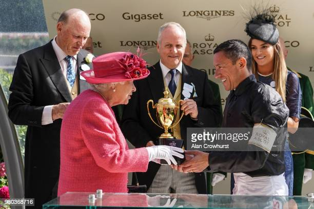 Queen Elizabeth II presents Frankie Dettori with his prize after he rode Stradivarius to win The Gold Cup on day 3 of Royal Ascot at Ascot Racecourse...