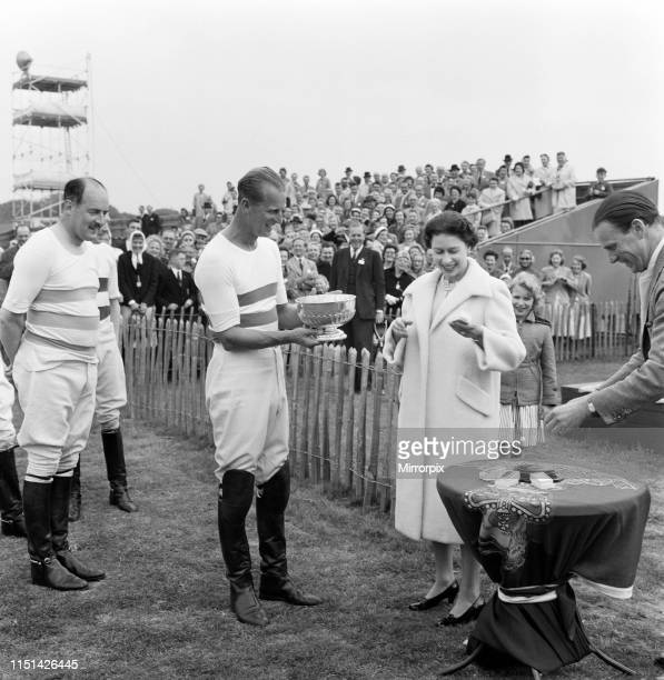 Queen Elizabeth II presents her husband Prince Philip Duke of Edinburgh with the Victoria Cup during the interval at polo at Windsor Great Park...