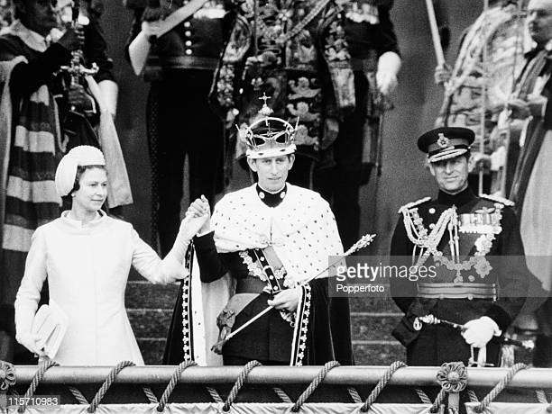 Queen Elizabeth II presents her son Prince Charles to the people of Wales after his investiture as the Prince of Wales with his father Prince Philip...