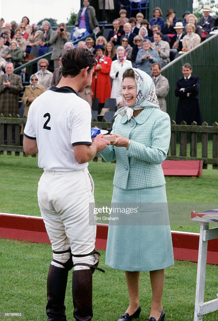 Queen Elizabeth II presents her son Prince Charles with a prize after a game of polo at Smith's Lawn, Windsor. (Exact day date not certain).