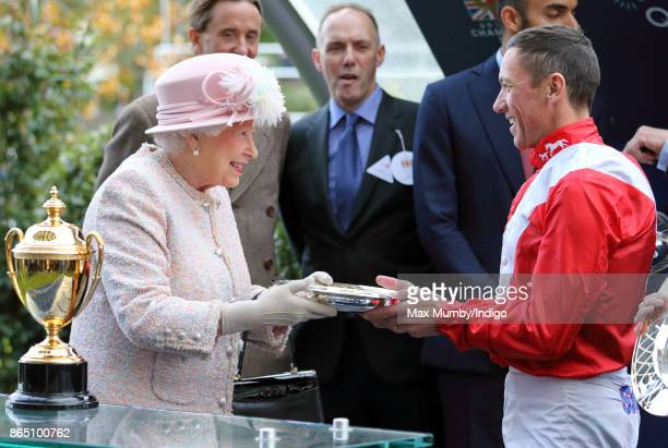 Queen Elizabeth II presents jockey Frankie Dettori with his prize for winning the Queen Elizabeth II Stakes on 'Persuasive' as she attends the QIPCO...