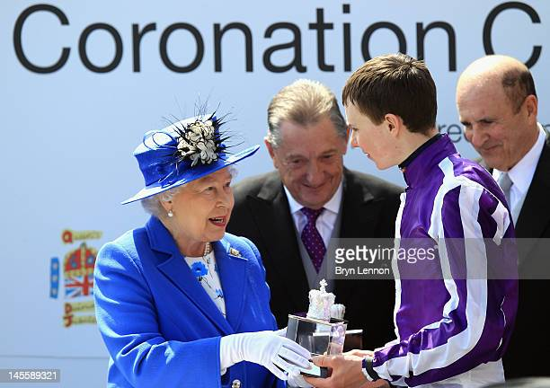 Queen Elizabeth II presents Joesph O'Brien with the trophy after winning the Coronation Cup at the Investec Derby at the start of the weekend marking...