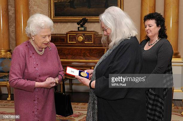 Queen Elizabeth II presents poet Gillian Clarke with her Gold Medal for Poetry watched by Poet Laureate Carol Ann Duffy , at Buckingham Palace on...