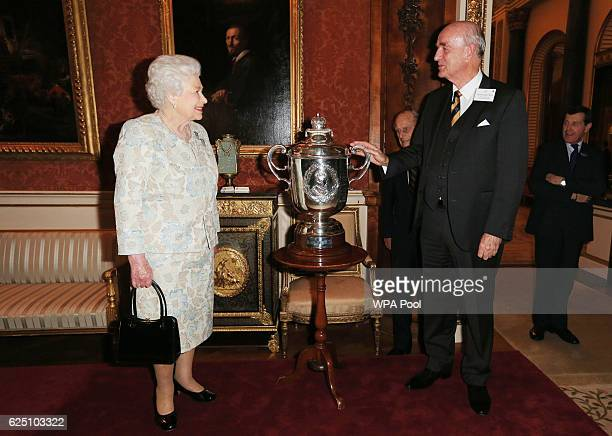 Queen Elizabeth II presents Professor John Pearn from Australia the King Edward VII Cup during a reception held for the Royal Life Saving Society at...