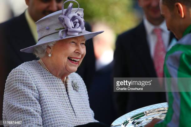 Queen Elizabeth II presents Sean Levey winner of The Queen Elizabeth II Stakes with his trophy during the QIPCO British Champions Day at Ascot...