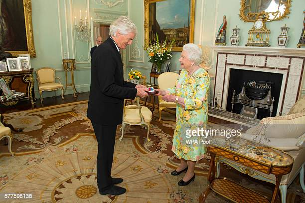 Queen Elizabeth II presents Sir James Dyson with the insignia with the insignia of members of the Order of Merit during a private audience at...