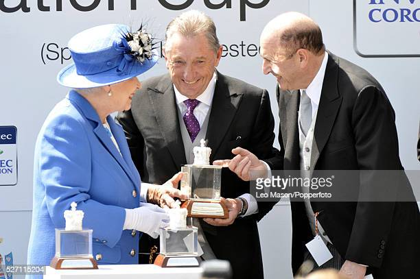 Queen Elizabeth II presents the Coronation Cup to owners Derrick Smith and Michael Tabor after their horse St Nicholas Abbey ridden by Joseph O'Brien...