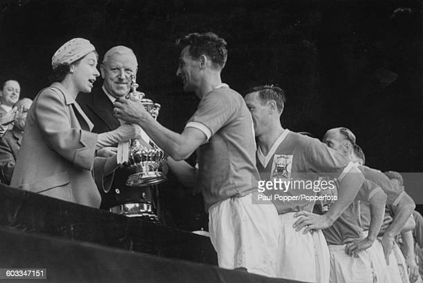 Queen Elizabeth II presents the FA Cup to Jack Burkitt captain of Nottingham Forest Football Club after his team defeated Luton Town 21 in the FA cup...