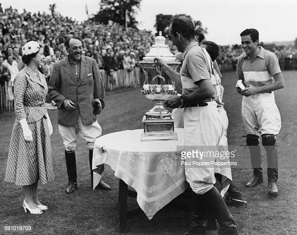 Queen Elizabeth II presents the polo Coronation Cup to Juan Alberdi, on behalf of the Argentine team, after they beat England by seven goals to six...