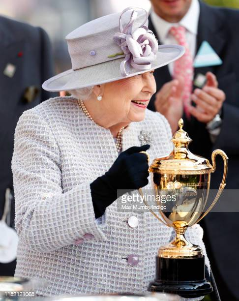 Queen Elizabeth II presents the Queen Elizabeth II Stakes trophy as she attends QICPO British Champions Day at Ascot Racecourse on October 19, 2019...