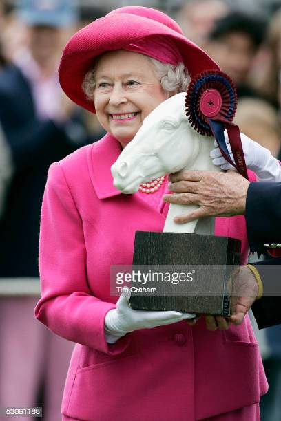 Queen Elizabeth II presents the Queen's Cup Trophy to the winning team at Guards Polo Club in Windsor